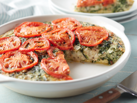 Spinach quiche in white serving dish topped with sliced